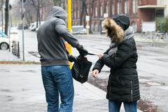 Male robber pulling purse from woman on sidewalk during winter - stock photo