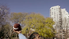 Man with dreadlocks throwing football in Washington Square Park with arch NYC Stock Footage
