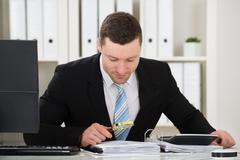 Male accountant analyzing invoice with magnifying glass at desk in office Stock Photos
