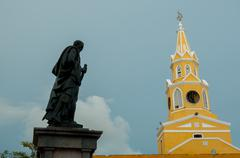 Black statue and yellow clock tower in front of a blue sky Stock Photos