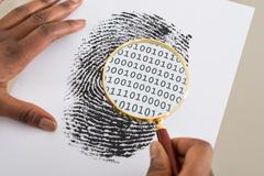 Close-up Of Person Using Magnifying Glass To Check Binary Code Within Finger  - stock photo