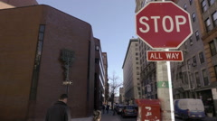 Red stop all way sign in Greenwich Village outside NYU building with Menorah NYC Stock Footage
