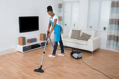 Young African Woman Cleaning Hardwood Floor With Vacuum Cleaner Stock Photos