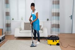 Smiling Young African Woman Cleaning Carpet With Vacuum Cleaner Stock Photos