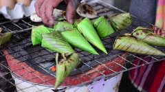 Sticky rice wrapped with banana leaf grilling on stove. Stock Footage