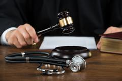 Midsection of judge striking mallet with stethoscope at desk in courtroom Stock Photos