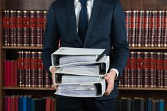 Midsection of male lawyer carrying stack of ring binders in courtroom - stock photo