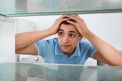 Amazed young man looking into empty refrigerator at home Stock Photos