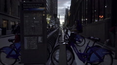 Citi Bikes bicycle docking station and meter with man walking toward sunset NYC Stock Footage