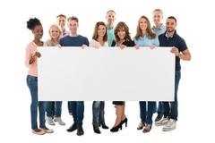 Full length portrait of confident creative business team holding blank billbo Stock Photos