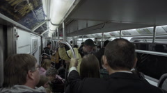 Crowded interior of subway train with passengers holding on to pole straphangers Stock Footage