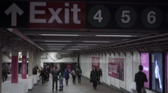 Exit sign in 4 5 6 lines subway station corridor with man in suit walking NYC Stock Footage