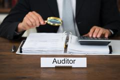 Midsection of male auditor scrutinizing financial documents at table in offic - stock photo