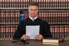Mature male judge reading document at desk against bookshelf in courtroom Kuvituskuvat