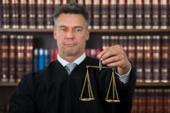 Stock Photo of Mature male judge holding justice scale against bookshelf in courtroom