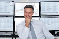 Portrait of confident stock market broker leaning on desk at office Stock Photos
