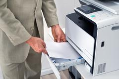 Midsection of businessman using printer in office - stock photo