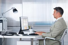Side view of male accountant using computer at desk in office - stock photo