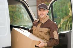 Stock Photo of Portrait of young delivery man removing cardboard box from truck