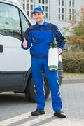 Portrait of smiling pest control worker showing thumbsup while standing by tr Stock Photos