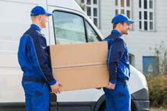 Stock Photo of Side view of young delivery men carrying cardboard box while walking by truck