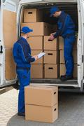 Delivery man unloading cardboard boxes from truck while colleague writing on  Kuvituskuvat
