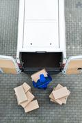 Directly above shot of delivery man unloading cardboard boxes from van on str - stock photo