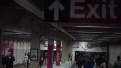 Tight shot on exit sign in subway station corridor with commuters and travelers Stock Footage