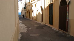 Old man walking in characteristic small street in Gallipoli, Italy Stock Footage