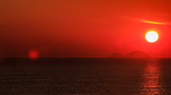 View of big sun disk sun-path across sea against blurry islands Stock Footage