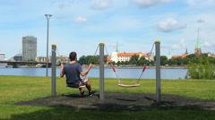 Man swinging on swing, watching riga view, latvia Stock Footage