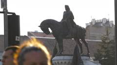 People passing by the statue of Matthias Corvinus in Cluj-Napoca Stock Footage