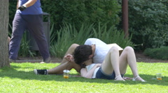 Couple lying down on grass in Iulius Park, Cluj-Napoca Stock Footage