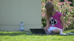 Girl sitting on grass and working on laptop in Iulius Park, Cluj-Napoca Stock Footage