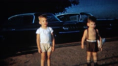 1959: Chickens roam free behind toddler boys in parking lot. PORTLAND, OREGON Stock Footage