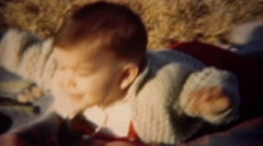 1951: Boy practicing tummy time in sunshine on warm blanket. LINCOLN, NEBRASKA Stock Footage