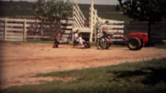 1951: Odd farm riding lawnmower pulling train of children in wagons.  LINCOLN, - stock footage