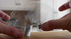 A man plays with a slinky Stock Footage