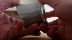 A mans hands play with a slinky Stock Footage