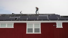 A timelapse of crews placing solar panels on the roof of a house - stock footage