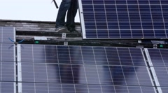 Crews placing solar panels on a roof of a house - stock footage
