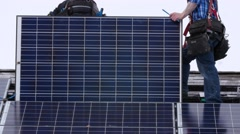 Editorial a crew placing solar panels on roof Stock Footage