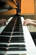 Women's hands on the keyboard of piano. girl plays music - stock photo