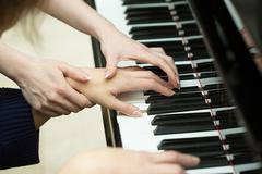 Stock Photo of Women's hands on the keyboard of piano. girl plays. music teacher