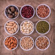 Mixed beans , lentils and nuts in the white bowl on brown cloth sack  backgro - stock photo