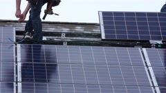Editorial a crew placing solar panels on the roof of house Stock Footage