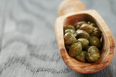 Marinated capers in olive scoop on wood table Stock Photos
