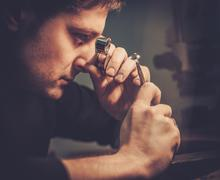 Portrait of a jeweler during the evaluation of jewels. Stock Photos
