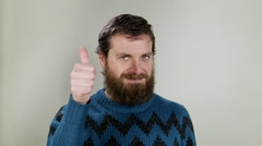 Hipster man showing thumbs up, saying ok. Close up on neutral background - stock footage