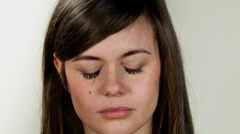 Emotional person. Young crying girl on neutral background Stock Footage